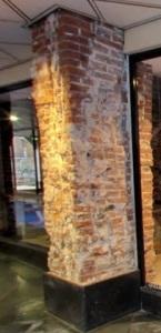 Zuilen met baksteenlagen uit verschillende perioden zijn in de winkelpassage te zien.
